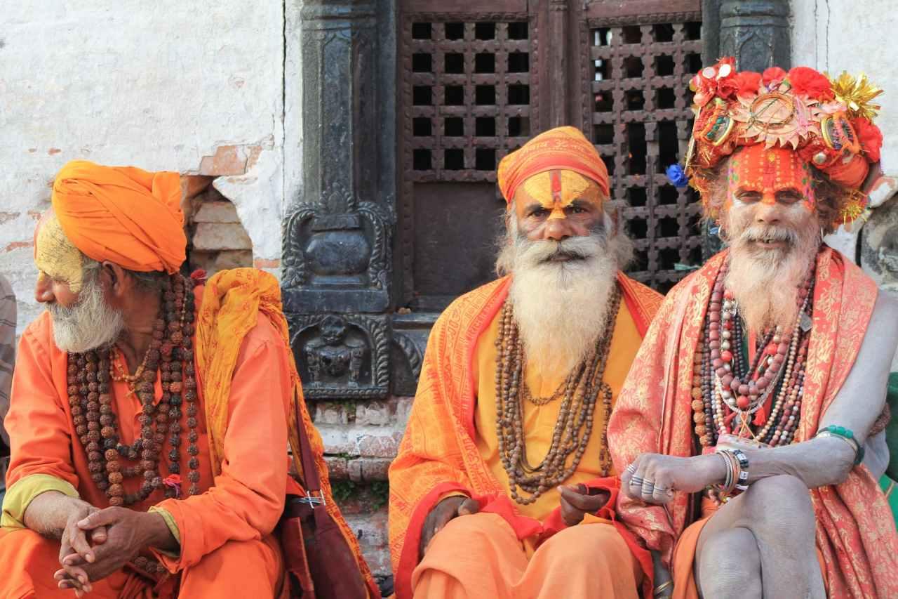 three men wearing orange tradition clothes